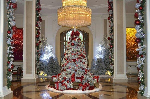 grosser-Saal-prachtvoller-Tannenbaum-künstlich-weiss-silbern-roter-Schmuck-Geschenke-Girlanden-Kronleuchter-Kristalle
