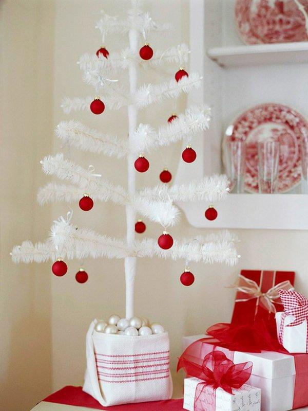 kleiner-dekorativer-weisser-Tannenbaum-rote-Kugeln-Dekoration-Geschenke