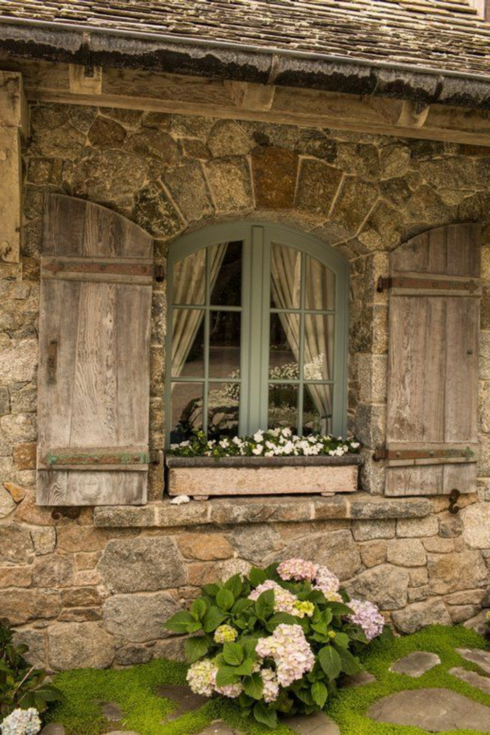 kleines-Haus-Steinwände-normandische-Architektur-Fenster-Blumentopf-Fensterladen-Holz