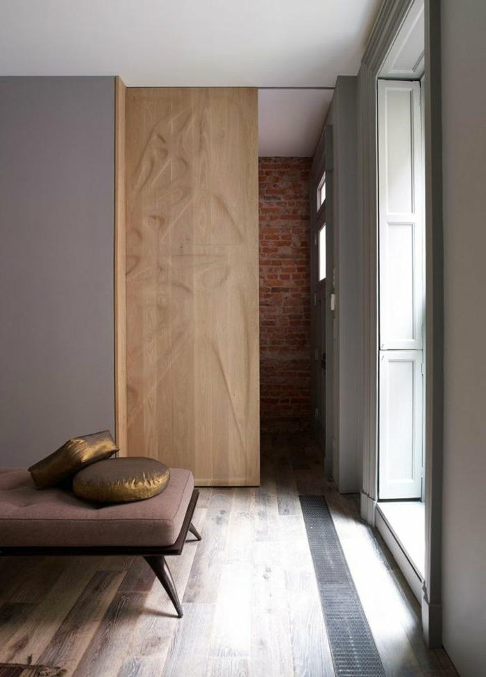 kreative-Schlafzimmer-Gestaltung-hölzerne-Tür-Ziegelwand-brauner-Liegestuhl-goldene-Kissen