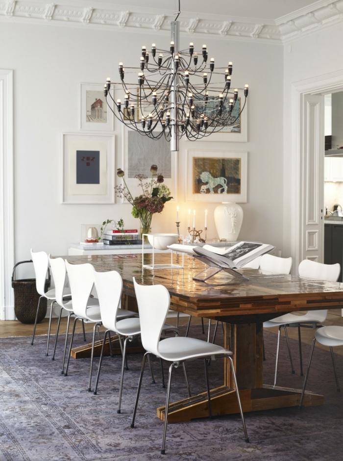 modernes-Interieur-weiße-Designer-Stühle-rustikaler-Tisch-großartiger-Kronleuchter-Landhausstil