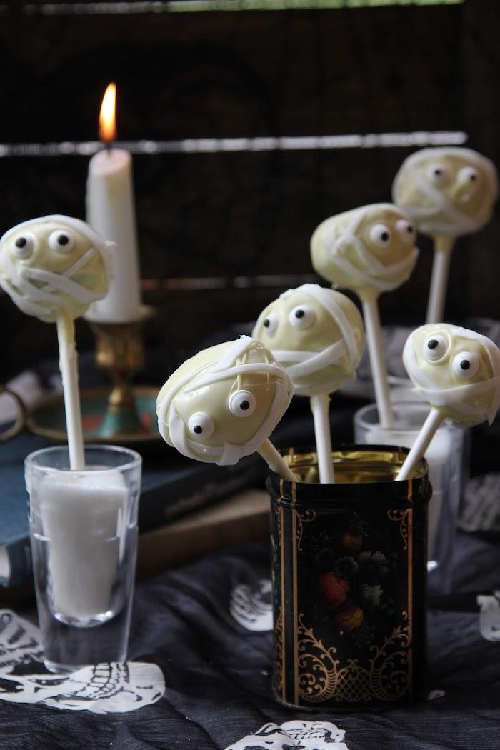 mumien cookies kleine kuchen stange weiße schokolade halloween rezepte fü kinder gruselige dekoration schwarze tischdecke mit schädeln