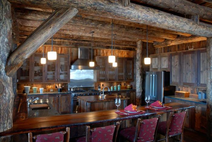 räumliche-Küche-landhausstil-möbel-Geräte-hängende-Leuchten-rote-rustikale-Stühle-Weingläser-Tischdekoration