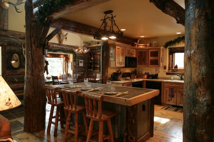 räumliche-Küche-moderne-Landhausmöbel-Kochinsel-Esstisch-rustikale-Stühle-Geweih-Kronleuchter