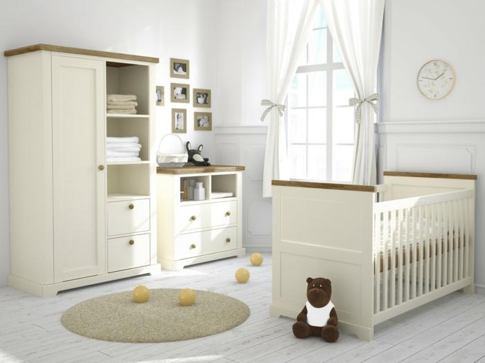 sympatisches-Kinderzimmer-Möbel-Creme-Farbe-Babybett-Schrank-Kommode-Plüschtiere-Wanduhr-kokette-Gardinen-Bälle