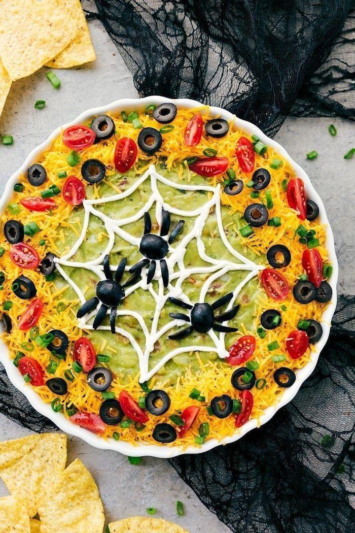 vorspeisen ideen spinnennetz avocado dip mit käse tomaten schwarze oliven dekoration schwarze spinnen halloween buffet