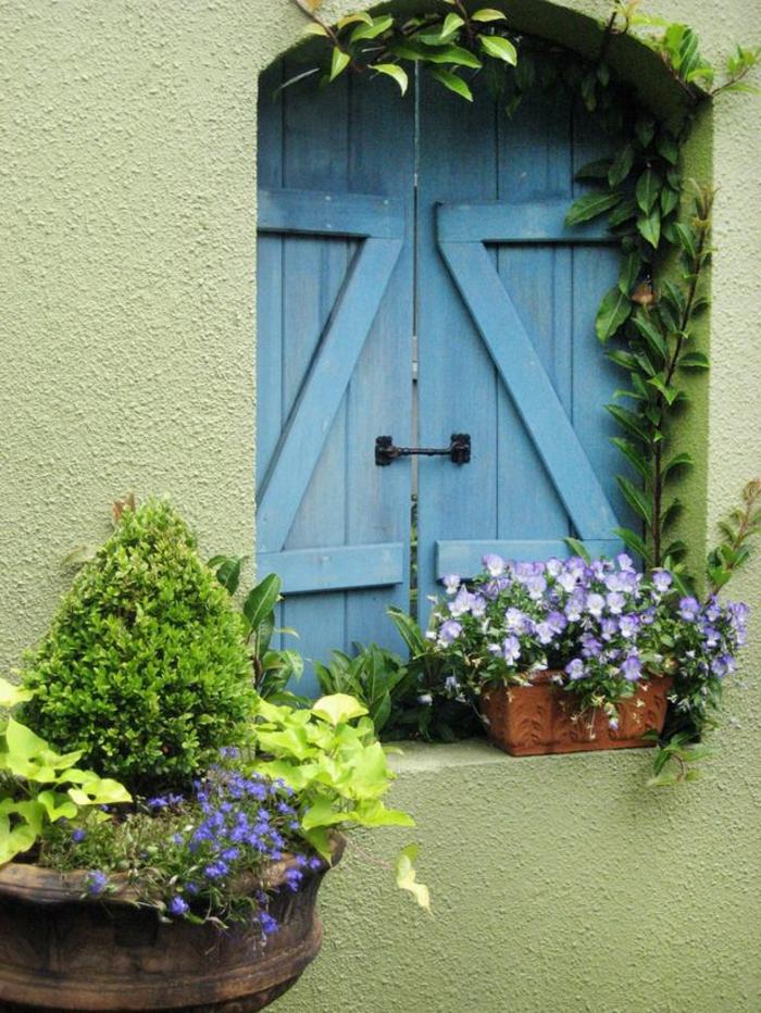 wunderschöne-blaue-Fensterläden-Blumen-grüne-Wand