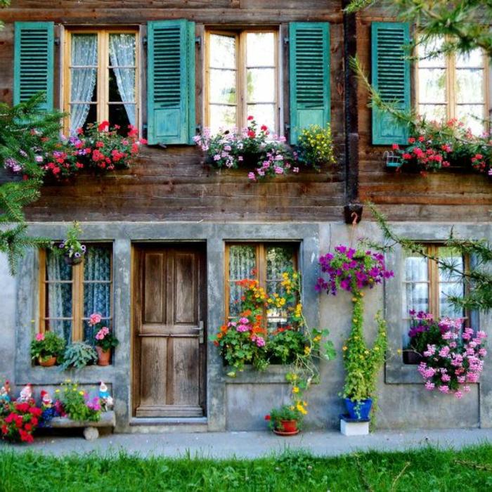 zweistöckiges-Haus-Schweizer-Alpen-Fenster-bunte-Läden-viele-Blumen-romantisch-gemütlich