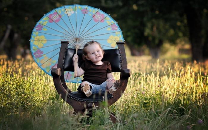 Baby-Mädchen-Sessel-im-Gras-kokettes-Modell-Kinderschirm