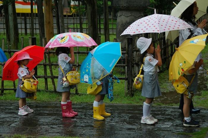 Kinder-bunte-kinderregenschirme-Reihe-Regen