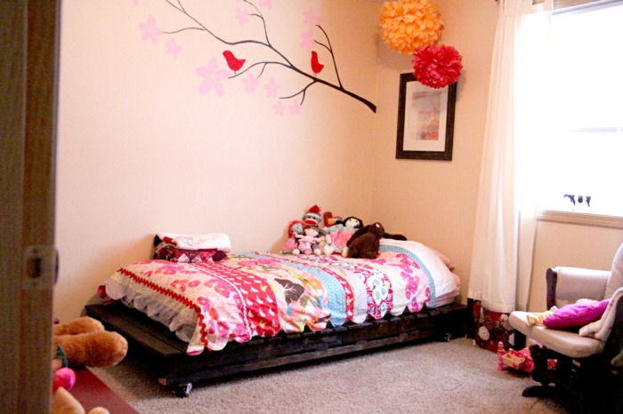 Kinderzimmer-Europaletten-bett-selber-bauen-Rollen-viele-Puppen-Plüschtiere-Papierblumen-Dekoration