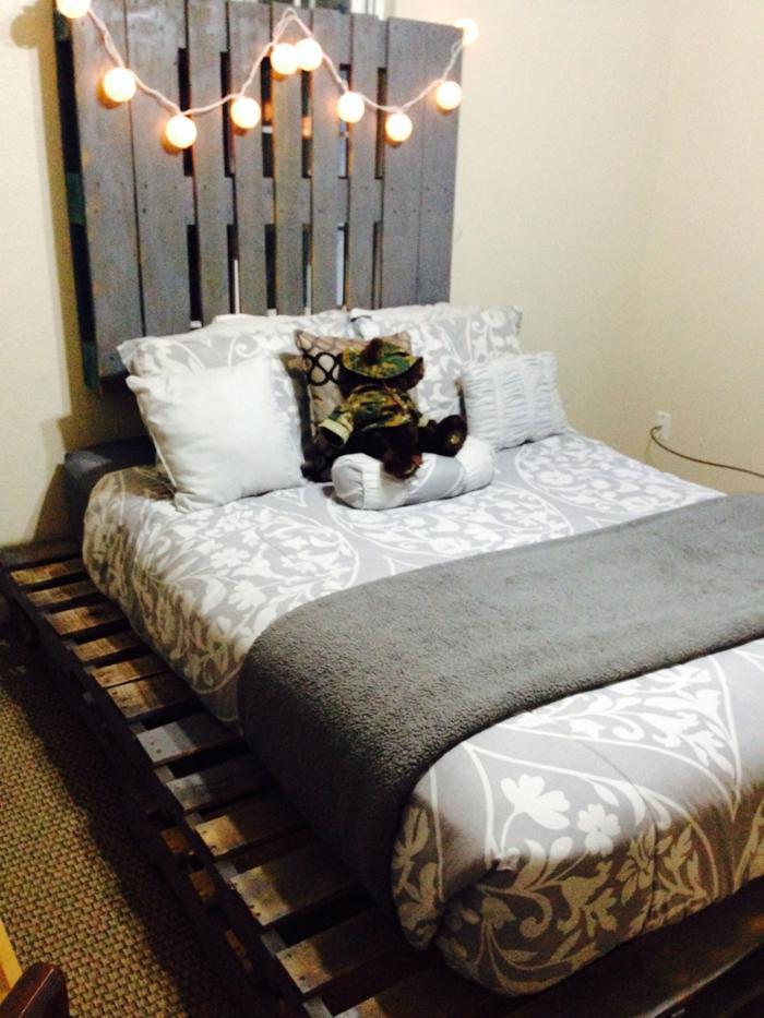 Kopfbrett-Bett-aus-paletten-hängende-Glühbirnen-schlichtes-Schlafzimmer-Interieur-graue-Schlafdecke