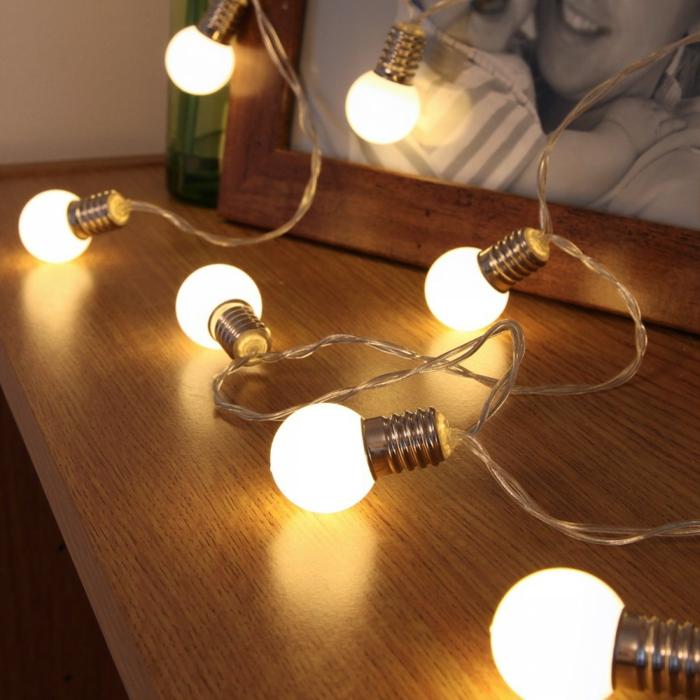 Lampe-Glühbirnenform-neben-bilderrahmen