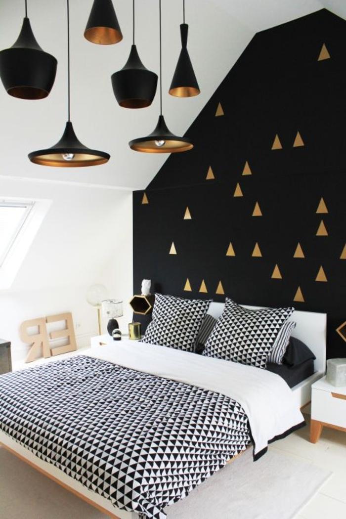 Schlafzimmer-schwarz-weißes-Interieur-Dreiecken-Motive-goldene-Elemente-schwarze-Designer-Leuchten