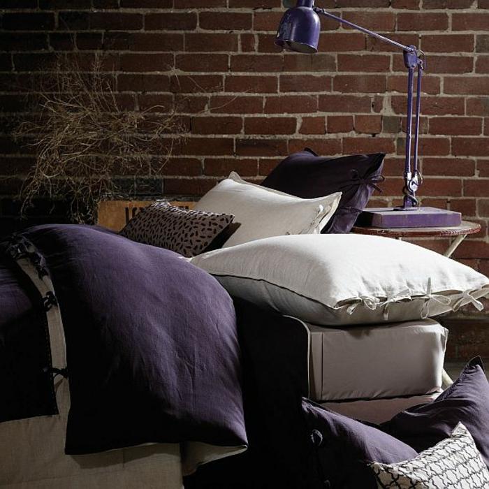 Sofa-stilvolle-Kissen-Ziegelwand-lila-Leselampe