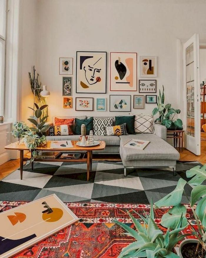 Gemalte Bilder und abstrakte bunte Bilder, farbiger und geometrischer Teppich, Ecksofa in grau mit Kissen,