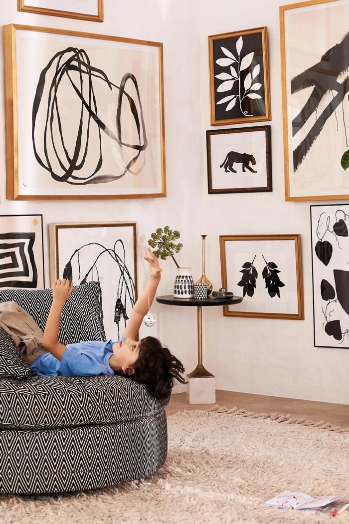 Wand dekoriert mit verschiedenen Bildern, Bilder mit Rahmen, Kind im blauen Hemd auf Sofa. Schwarz-weiße Zeichnungen