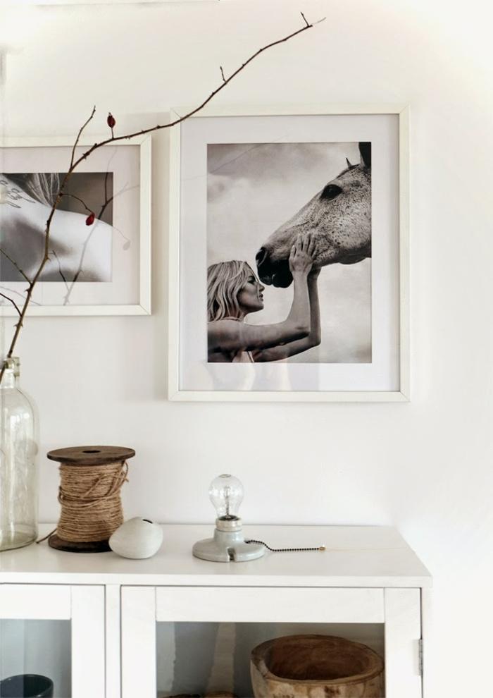 Großes Foto von einer Frau und einem Pferd in schwarz und weiß, Bilder mit Rahmen, weiße Kommode, Zweig vom Baum in Vase