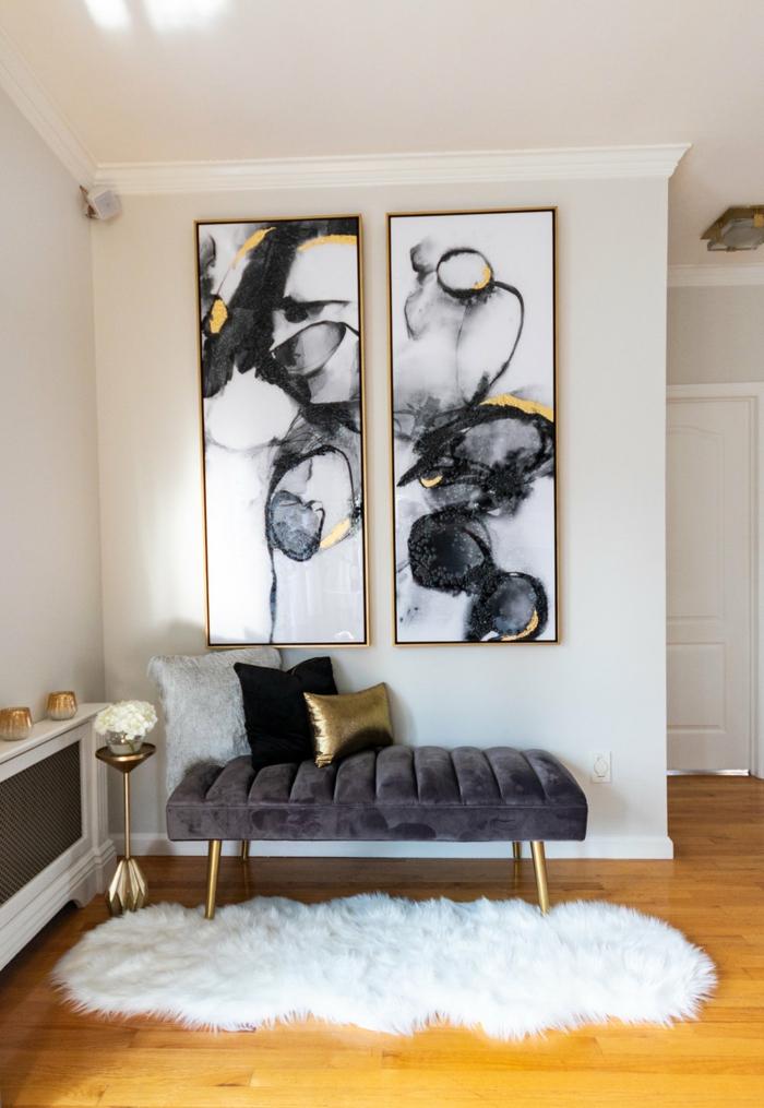 Leinwandbilder Wohnzimmer, zwei gemalte Bilder in schwarz weiß mit gelbem Motiv, Liege in dunkelgrau mit Kissen, flauschiger Teppich