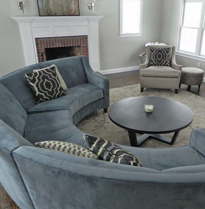 blaues-halbrundes-Sofa-graphische-Kissen-schlichtes-Wohnzimmer-Interieur-Kamin