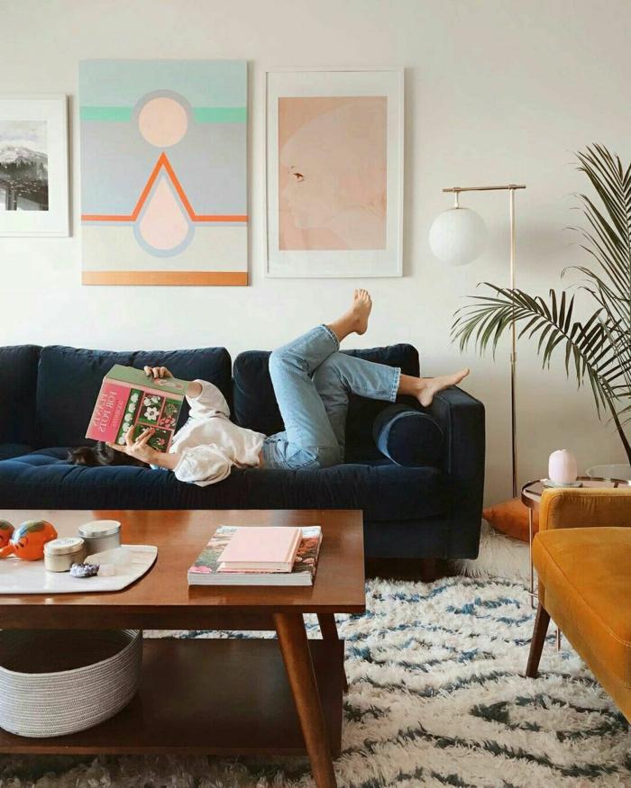 Frau in Jeans und weißes Top auf blauem Sofa, Wandbilder Wohnzimmer mit geometrischen Figuren, Bild von einem Gesicht