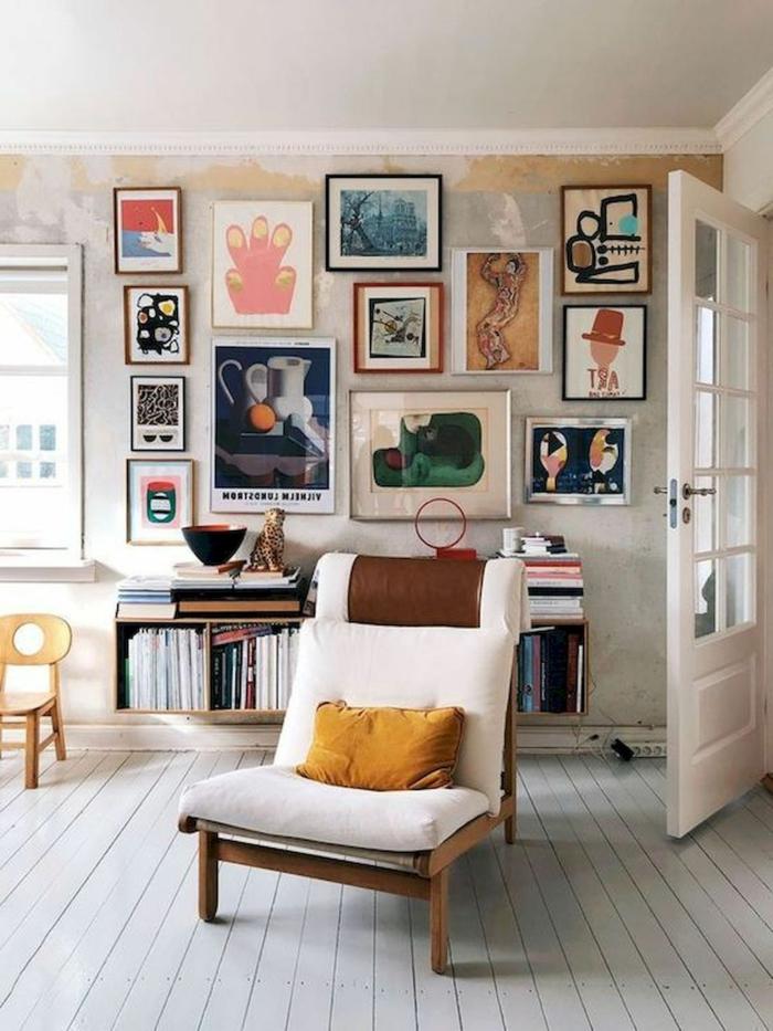Bunte Bilder artistisch gestaltet auf Wand, gemalte Bilder, Sessel aus Holz mit weißem Kissen, kleiner Stuhl in gelb, kleine Kommode mit Magazine