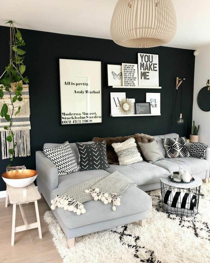 Großes Ecksofa in grau, dunkelblaue Wand mit aufgehängten Bildern mit Zitate, moderne Bilder, flauschiger Teppich