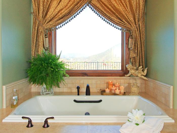 elegantes-Interieur-kleines-Badezimmer-dekoideen-goldene-Engelfigur-Kerzen-Wasserlilie-Grün-aristokratische-Vorhänge