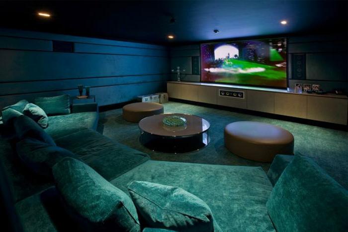 elegantes-innovatives-Wohnzimmer-Interieur-großer-Fernseher-grüne-xxl-couch-Samt-halbrundes-Sofa