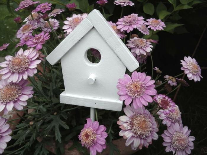 gartendeko-aus-holz-dekoratives-weißes-vogelhäuschen-rosa-Blumen