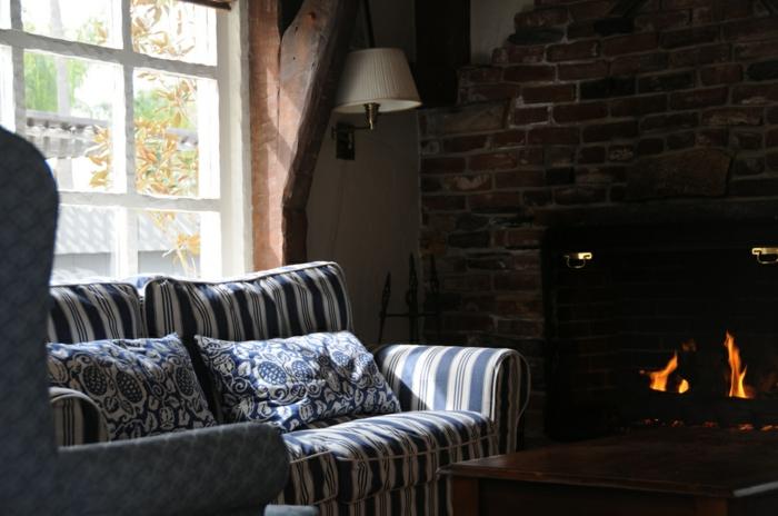 gemütliche-Zimmer-Einrichtung-Kamin-Sofa-Leselampe