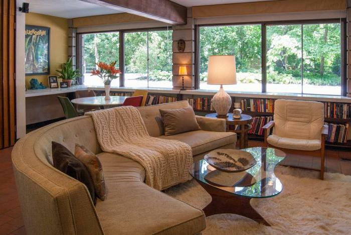 gemütliches-Wohnzimmer-Interieur-halbrunde-Couch-gestrickte-Schlafdecke-Ledersessel