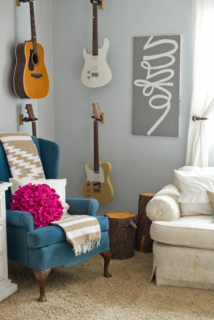 gemütliches-Wohnzimmer-Sessel-mit-feinem-Design-artistisches-Wandbild-elektronische-Akustik-Gitarre-an-der-Wand