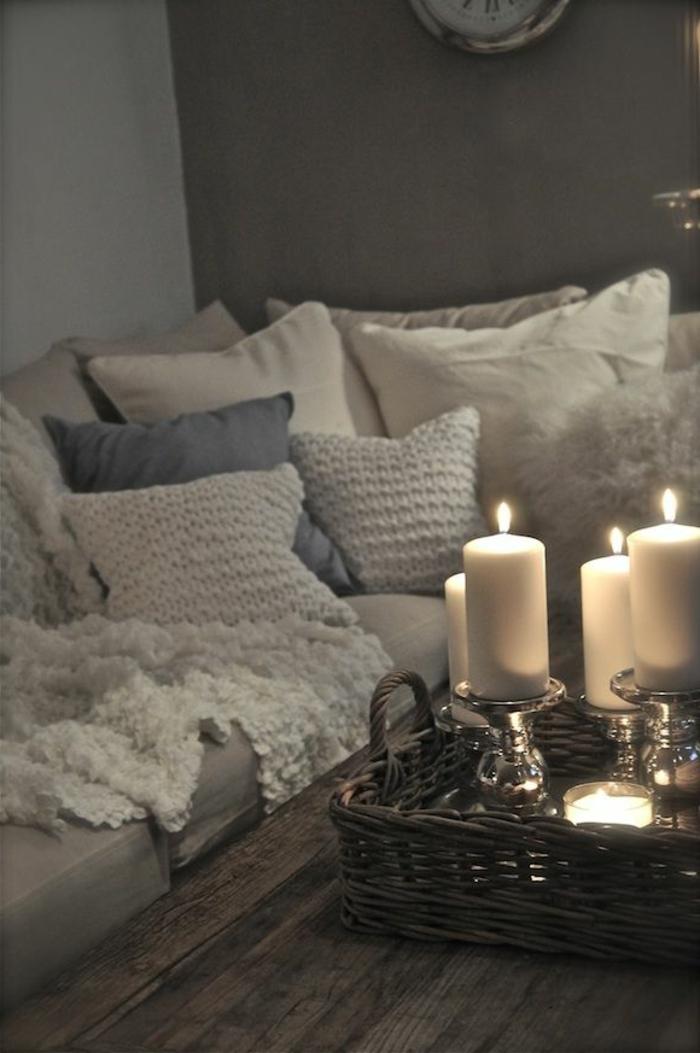 gemütliches-Wohnzimmer-Sofa-viele-Kissen-gestrickte-Modelle-weiche-Nuancen-Kerzen-romantische-Atmosphäre