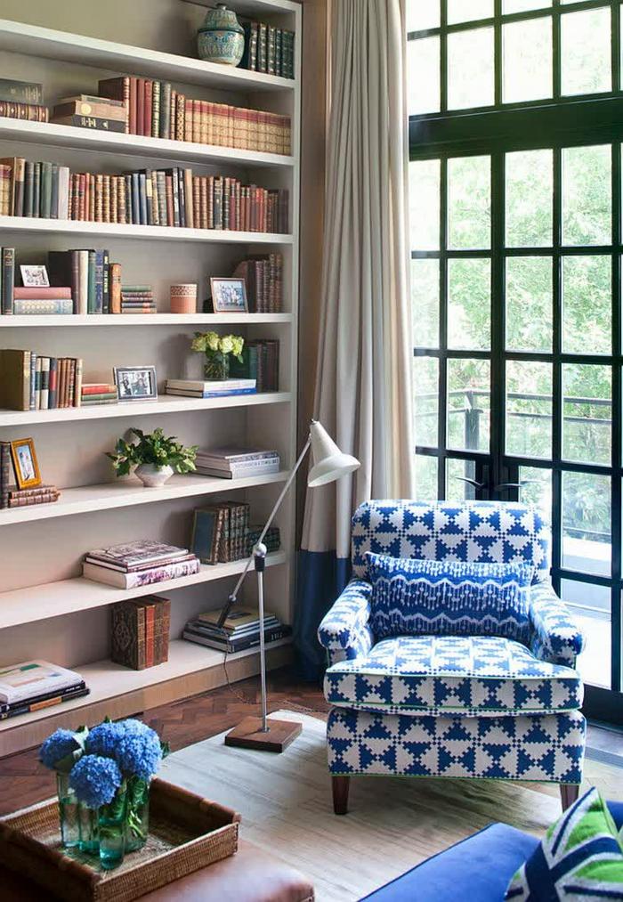 gemütliches-Wohnzimmer-große-Bücherwand-lila-Blumen-Leselampe-schöner-Sessel