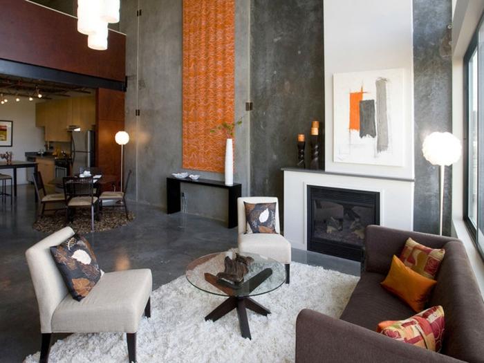 gemütliches-Wohnzimmer-raues-Interieur-Beton-Marmor-graue-Nuancen-Kamin-orange-Akzente-Teppich-weiß