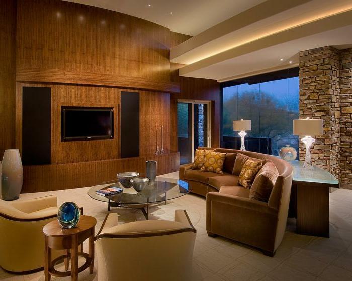 gemütliches-räumliches-Wohnzimmer-Möbel-Pastellfarben-Sessel-braunes-Sofa-halbrunde-Form