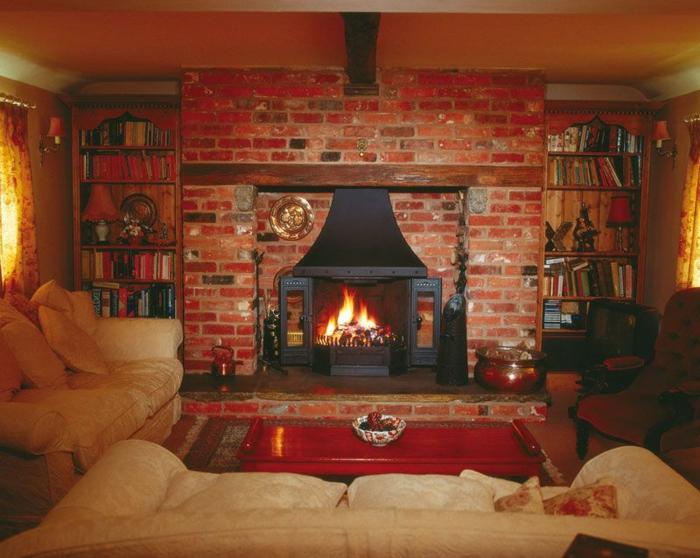 gemauerter-kamin-rote-gestaltung-große-sofas