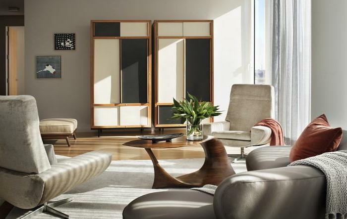 graues-Sofa-halbrund-orange-Kissen-schlichtes-Wohnzimmer-Interieur
