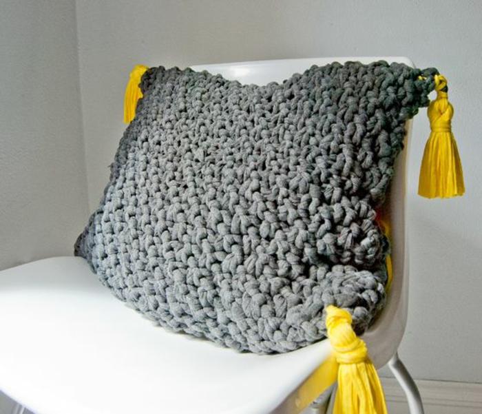 graues-gestricktes-Kissen-mit-gelben-Quasten-exotisches-Modell