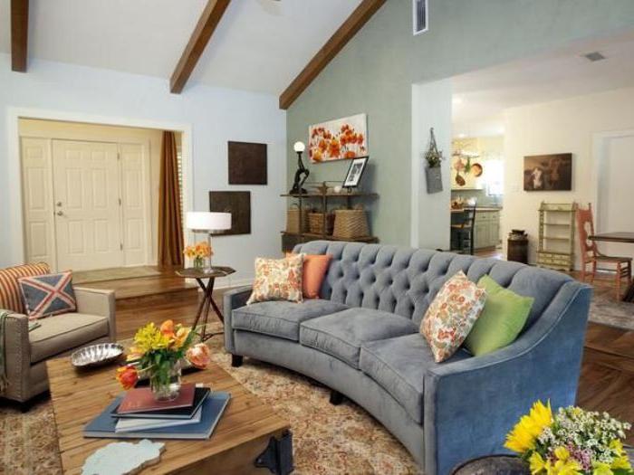 graues-halbrundes-Sofa-Samt-bunte-Kissen-Blumen-gemütliche-Atmosphäre