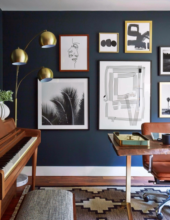 dunkelblaue Wand mit aufgehängten Bildern und Linienzeichnungen, moderne Bilder, Klavier in braun, geometrischer Teppich
