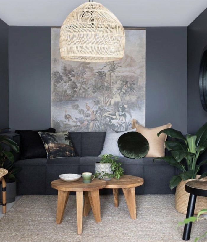 Gemälde an die Wand, große Wandbilder von Dschungel auf dunkle Wand, zwei Tische aus Holz
