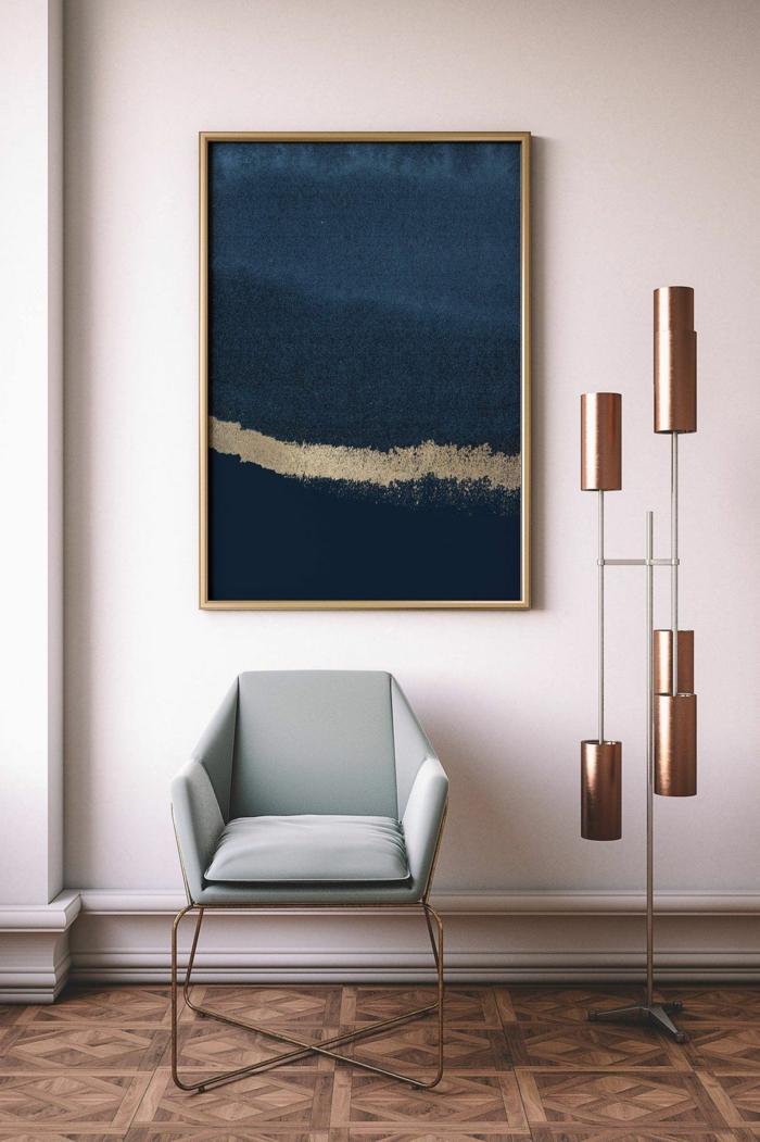 gemalte Bilder in blau und gold, modische Kunst, Bild aufgehängt an rosa Wand, Sessel in grau-grün, interessante Lampe