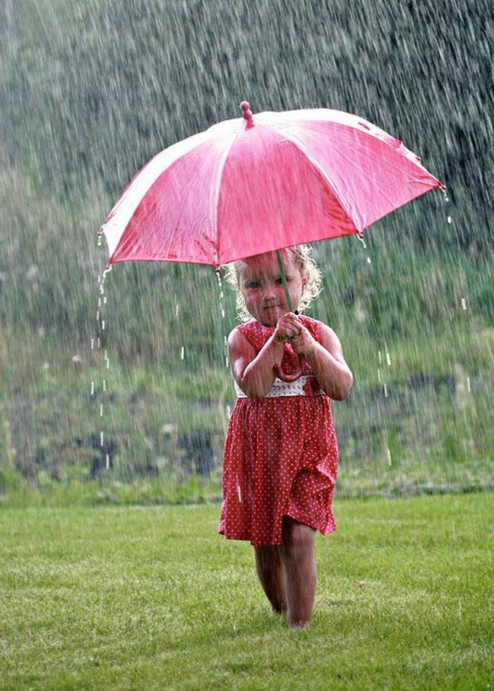 kleines-Baby-läuft-mit-rosa-Regenschirm