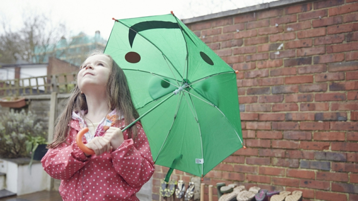 kleines-Mädchen-grüner-kinderregenschirm-regnerischer-Tag