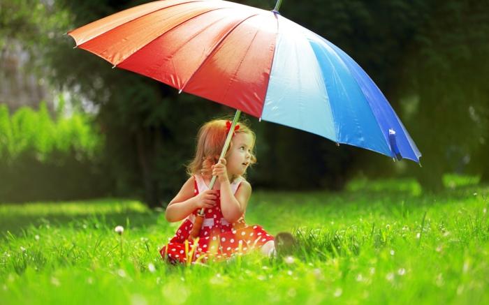 kleines-Mädchen-im-Gras-mit-großem-regenschirm