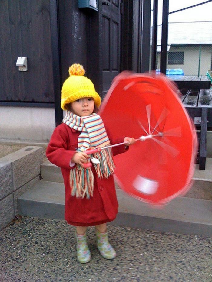 kleines-süßes-Mädchen-roter-Mantel-bunter-Schal-roter-kinderregenschirm