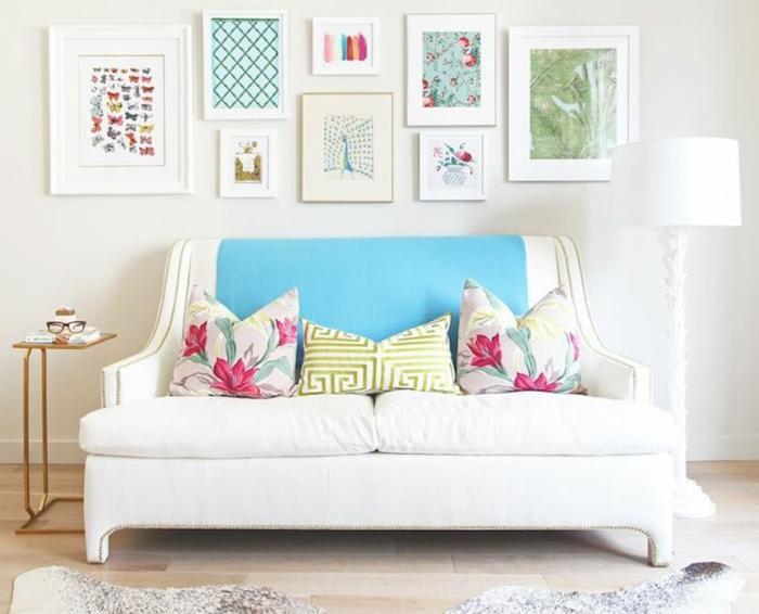 kreatives-Interieur-weißes-Sofa-Kissen-florale-Motive-artistische-Wandbilder-schöne-elegante-Leselampe