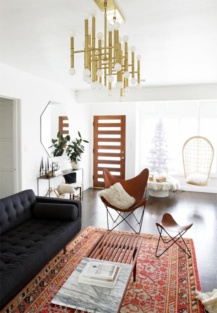kreatives-Wohnzimmer-Interieur-schwarzes-Sofa-bequeme-Desoigner-Sessel-vintage-Leuchten-Teppich-orientalisches-Muster